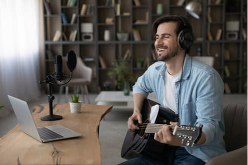 Dude playing his guitar in front of his laptop with blogging for musicians and how to start your own music blog